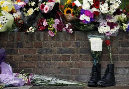 A pair of army boots with floral tributes for Drummer Lee Rigby, of the British Army's 2nd Battalion The Royal Regiment of Fusiliers, are lined at a security fence outside army barracks near the scene of his killing in Woolwich, southeast London May 24, 2013. REUTERS/Luke MacGregor