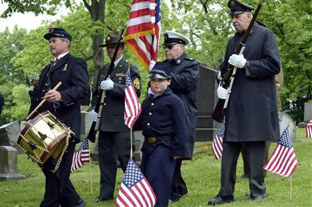 Jim Smith (L), 70, of Hempfield, leads members of the Grand Army of the Republic Post 88, Pittsburgh, and the Armbrust Veterans and Civil War Re-enactors, including Luke Prohaska (C) in a Civil War uniform, for a ceremony at the graveside of Peter Guibert, a Union Civil War drummer boy, in Pittsburgh, Pennsylvania May 24, 2013. REUTERS/Jeffrey B. Roth