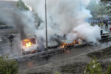 5月23日、スウェーデンの首都ストックホルム郊外で起きた暴動は、同国の「移民寛容政策」の負の一面を浮き彫りにした。写真は消火に当たる消防隊員ら(2013年 ロイター/Scanpix)