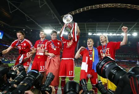 Bayern Munich's Jerome Boateng (4th L) lifts the trophy while celebrating with team mates in front of photographers after defeating Borussia Dortmund in their Champions League Final soccer match at Wembley Stadium in London May 25, 2013. REUTERS/Darren Staples