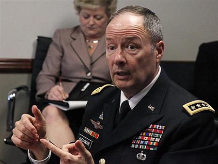 An aide (L) takes notes as U.S. General Keith Alexander, director of the National Security Agency (NSA) and U.S. Cyber Command, speaks to reporters during the Reuters Cybersecurity Summit in Washington, May 14, 2013. REUTERS/Stelios Varias