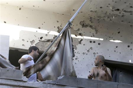 Two men inspect their damage house after two rockets hit their area in a Beirut suburbs May 26, 2013. REUTERS-Mohammed Azakir