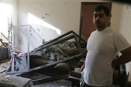 A man stands in his damaged house after two rockets hit houses and a car sales yard in Beirut suburbs May 26, 2013. REUTERS-Mohammed Azakir