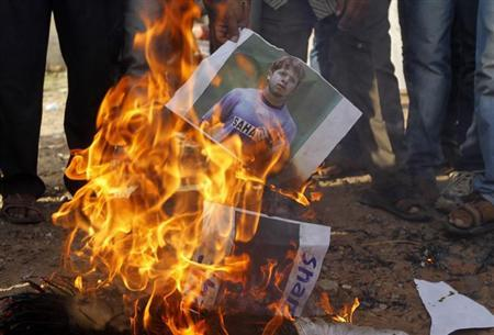 Demonstrators burn a poster of former India test bowler Shanthakumaran Sreesanth during a protest in the western Indian city of Ahmedabad May 16, 2013. REUTERS/Amit Dave