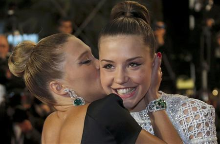 Cast member Lea Seydoux (L) kisses cast member Adele Exarchopoulos as they pose on the red carpet arriving for the screening of the film ''La Vie D'Adele'' in competition during the 66th Cannes Film Festival in Cannes May 23, 2013. REUTERS/Regis Duvignau