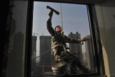A labourer cleans the window of an office building near a residential complex (back) under construction in Shenyang, Liaoning province May 17, 2013. REUTERS/Stringer