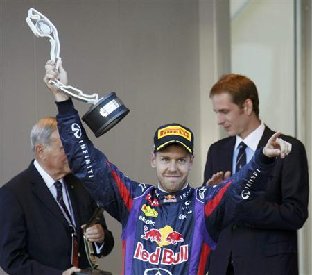 Red Bull Formula One driver Sebastian Vettel of Germany gestures with his trophy as he celebrates after finishing second in the Monaco F1 Grand Prix May 26, 2013. REUTERS/Robert Pratta