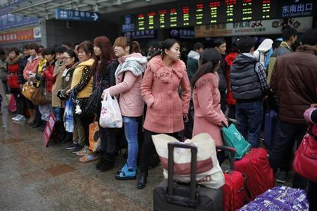 Migrant workers make their way to Shanghai railway station, the meeting point where an online employment agency arranged to pick them up to their new jobs, in Shanghai February 26, 2013. REUTERS/Aly Song