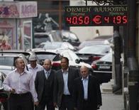 """Люди проходят мимо вывески обменного пункта в Москве 9 августа 2011 года. Рубль незначительно подорожал утром понедельника, в фокусе рынков уплата крупных налогов 27-28 мая, из-за чего российская валюта может получить поддержку от продаж экспортной выручки расчетами """"завтра"""". REUTERS/Grigory Dukor"""