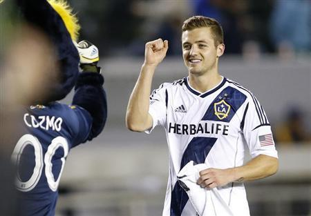 Los Angeles Galaxy midfielder Robbie Rogers (R) fist pumps the team's mascot Cozmo after playing in the second half of the MLS soccer game against the Seattle Sounders in Carson, California May 26, 2013. REUTERS/Danny Moloshok