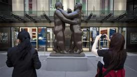 "Fernando Botero's ""Dancers"" is photographed by a passer-by as it sits in front of Christie's Auction House in New York, May 27, 2013. REUTERS/Carlo Allegri"