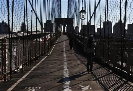 A woman walks across the Brooklyn Bridge in New York January 24, 2013. REUTERS/Shannon Stapleton/Files