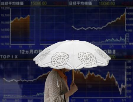 A woman using a parasol walks past a stock quotation board outside a brokerage in Tokyo May 15, 2013. REUTERS/Toru Hanai