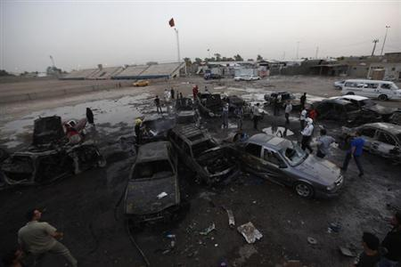 Residents gather at the site of bomb attacks in Baghdad May 27, 2013. More than 70 people were killed in a wave of bombings in markets in Shi'ite neighbourhoods across Baghdad on Monday in worsening sectarian violence in Iraq. REUTERS/Thaier al-Sudani