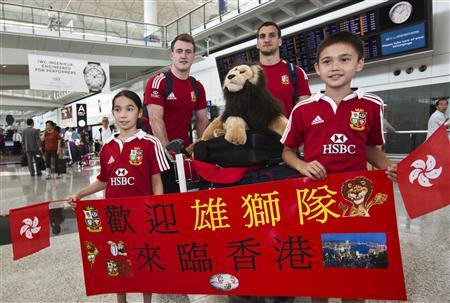 Young fans pose with British and Irish Lions' full-back Stuart Hogg (2nd L), captain Sam Warburton (2nd R) and stuffed lion''Bil'', the team's mascot, as they arrive at Hong Kong's International Airport May 28, 2013. REUTERS/Tyrone Siu