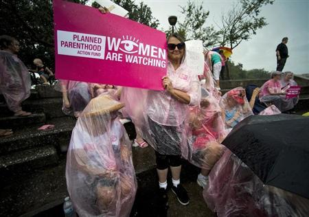 Planned Parenthood supporters Laurie Sullivan (L) and Leanne Walker (C) sit out a downpour during a rally outside the Republican National Convention in downtown Tampa, Florida, August 29, 2012. REUTERS/Steve Nesius
