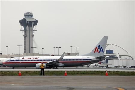 An American Airlines jet passes the Air Traffic Control Tower on the runway at Los Angeles International Airport (LAX), California April 24, 2013. REUTERS/Patrick T. Fallon