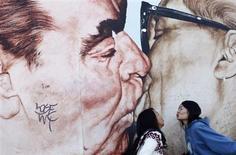 Китаянки целуются на фоне изображения Эриха Хоннекера и Леонида Брежнева на фрагменте Берлинской стены 3 октября 2012 года. Мемориальная табличка, посвященная советскому лидеру Леониду Брежневу, может быть восстановлена на фасаде здания в Москве, где жил генсек, став приметой ностальгии по советским временам, которую оседлал российский президент Владимир Путин. REUTERS/Lisi Niesner