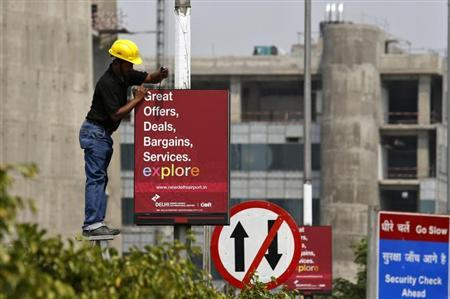 A worker removes a GMR Infrastructure board near to the airport in New Delhi, May 13, 2013. REUTERS/Anindito Mukherjee