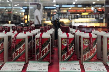 A customer walks past a glass case displaying Maotai liquors, a form of baijiu, with different price tags at a supermarket in Shenyang, Liaoning province, in this August 8, 2012 file photo. Chinese baijiu, a flammable, pungent white liquor averaging a 110-proof wallop, is the world's most consumed form of liquor thanks to its popularity in China, but for the first time distillers are looking to develop export markets.REUTERS-Stringer-Files