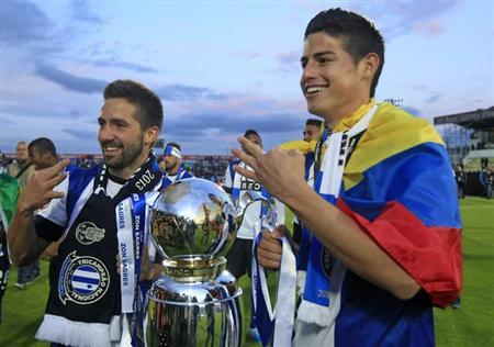 Porto's Joao Moutinho (L) and team mate James Rodriguez hold the trophy while they celebrate winning the Portuguese Premier League title after their soccer match against Pacos Ferreira at the Mata Real stadium in Pacos de Ferreira May 19, 2013. REUTERS/Jose Manuel Ribeiro