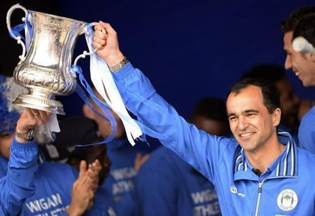 Wigan Athletic's manager Roberto Martinez holds up the cup during a victory parade after winning the English FA Cup in Wigan, northern England May 20, 2013. REUTERS/Nigel Roddis