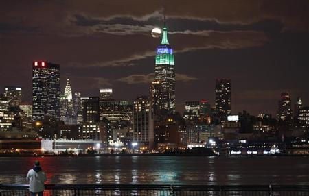 A full moon rises behind the Empire State Building in New York as a man watches in a park along the Hudson River in Hoboken, New Jersey, February 25, 2013. REUTERS/Gary Hershorn