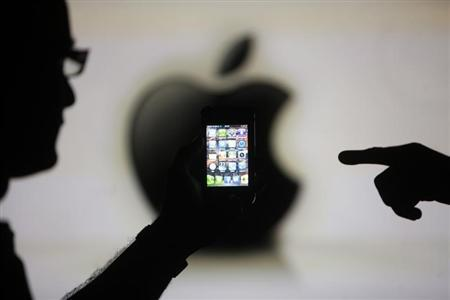 Men are silhouetted against a video screen with an Apple logo as they pose with an Apple iPhone 4 smartphone in this photo illustration taken in the central Bosnian town of Zenica, May 17, 2013. REUTERS/Dado Ruvic