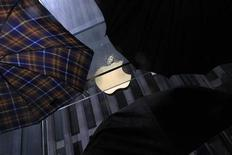 Люди с зонтами перед магазином Apple в Нью-Йорке 19 мая 2013 года. Apple Inc выпустит новые гаджеты, которые изменят правила игры на рынке, заявил исполнительный директор компании, создавшей планшетный компьютер и новый тип смартфона, Тим Кук. REUTERS/Eric Thayer