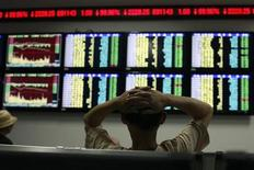 An investor reads information displayed on an electronic screen at a brokerage house in Shanghai July 30, 2012. REUTERS/Aly Song