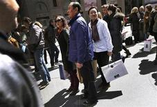 Chinese shoppers stand with shopping bags on a sidewalk along 5th Avenue in New York City, April 4, 2013. REUTERS/Mike Segar