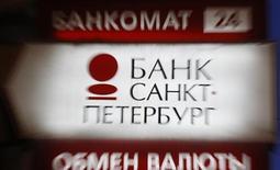 Вывеска пункта обмена валюты банка Санкт-Петербург в Санкт-Петербурге 25 марта 2013 года. Чистая прибыль банка Санкт-Петербург, рассчитанная по международным стандартам, в первом квартале 2013 года увеличилась до 1,1 миллиарда рублей со 123,3 миллиона в первом квартале 2012 года, превысив консенсус-прогноз аналитиков благодаря росту розничного портфеля и снижению отчислений в резервы, сообщил банк в четверг. REUTERS/Alexander Demianchuk