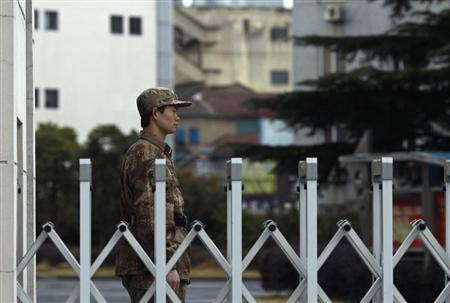 A Chinese People's Liberation Army soldier stands guard in front of 'Unit 61398', a secretive Chinese military unit, in the outskirts of Shanghai, February 19, 2013. REUTERS/Carlos Barria