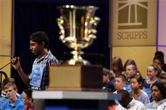 Ansun Sujoe, of Fort Worth, spells a word correctly behind the winner's trophy during the 2013 Scripps National Spelling Bee at the Gaylord National Resort and Convention Center at National Harbor in Maryland, May 29, 2013. REUTERS/Larry Downing