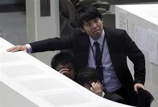 Сотрудники Токийской фондовой биржи смотрят на электронное табло с котировками 24 мая 2013 года. Азиатские фондовые рынки снизились в четверг из-за волнений, что ФРС скоро прекратит стимулировать экономику, и локальных факторов. REUTERS/Toru Hanai