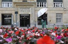 A women holding an umbrella stands in front of the Austrian central bank in Vienna May 27, 2013. REUTERS/Leonhard Foeger
