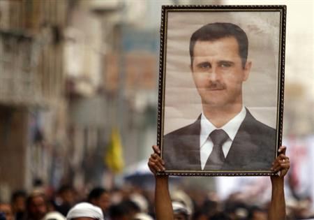 A Shi'ite anti-government protester holds up a poster of Syrian President Bashar al-Assad during a demonstration against Israeli air strikes in Syria, in Sanaa May 10, 2013. REUTERS/Khaled Abdullah
