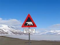 A sign warns residents of the arctic Svalbard islands in Norway of the danger from roaming polar bears, May 26, 2013. Svalbard in Norway's high Arctic, is home to 2,500 people and about 3,000 polar bears. Picture taken May 26, 2013. REUTERS/Balazs Koranyi