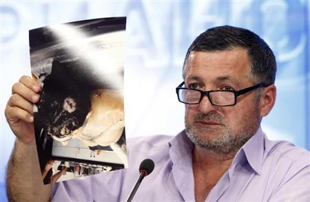 Abdulbaki Todashev, the father of Ibragim Todashev, shows photographs of his son's body at a mortuary during a news conference in Moscow May 30, 2013. REUTERS/Maxim Shemetov