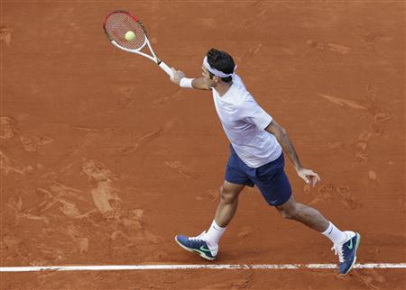 Roger Federer of Switzerland hits a return to Somdev Devvarman of India during their men's singles match at the French Open tennis tournament at the Roland Garros stadium in Paris May 29, 2013.