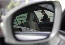 A visitor (R) and an employee of Toyota Motor Corp. are reflected on a side mirror of a car at the company show room in Tokyo May 8, 2013. REUTERS/Yuya Shino