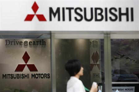 A woman walks in front of Mitsubishi Motors Corp's headquarters in Tokyo May 23, 2013. REUTERS/Toru Hanai