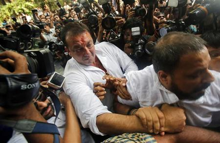 Bollywood actor Sanjay Dutt is escorted by his security staff as he arrives to surrender at a court in Mumbai May 16, 2013. REUTERS/Vivek Prakash