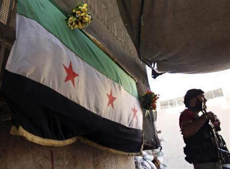 Free Syrian Army fighters hold their weapons while standing near an opposition flag at their post in Aleppo's Bustan al-Qasr, May 29, 2013. Picture taken May 29, 2013. REUTERS/Aref Hretani
