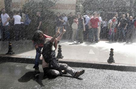 A demonstrator reacts as riot police use water cannon to disperse the crowd during a protest against the destruction of trees in a park brought about by a pedestrian project, in Taksim Square in central Istanbul May 31, 2013. REUTERS-Osman Orsal