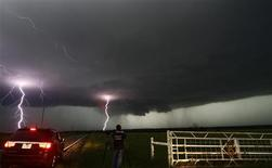 Cloud to ground lightning strikes near storm chasers during a tornadic thunderstorm in Cushing May 31, 2013. Violent thunderstorms on Friday produced tornadoes in central Oklahoma that killed five people including a mother and her baby and menaced Oklahoma City and its hard-hit suburb of Moore, authorities said. REUTERS/Gene Blevins