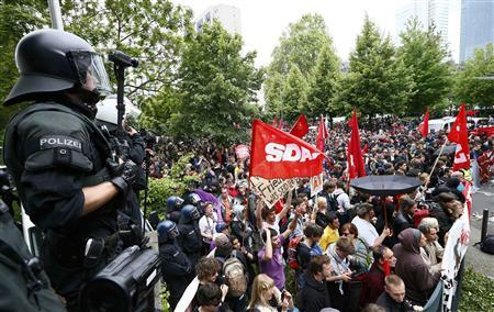 Riot police stand guard in front of protesters during an anti-capitalism 'Blockupy' demonstration in Frankfurt June 1, 2013. REUTERS-Ralph Orlowski