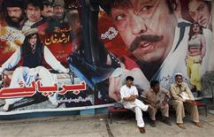 Cinema workers sit near a poster of a Pashto movie at Arshad cinema in Peshawar May 27, 2013. Pashto cinema, or Pollywood, which once made its home in Peshawar, is now confined to a handful of theatres that haven't been attacked by Islamists. The Taliban banned cinema and music during their five-year rule in neighbouring Afghanistan, deeming them un-Islamic, and insisted that women wear all-enveloping burqas. The Pakistani Taliban are just as strict and in Pashto cinema, where there is no sex or even kissing and only a bit of midriff on show, all their rules are broken. Picture take May 27, 2013. To match Feature PAKISTAN-CINEMA/ REUTERS/Zohra Bensemra