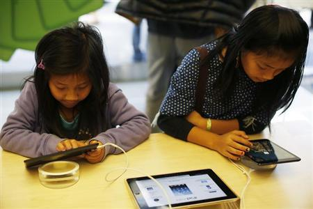 Two children use the iPad Mini at the Apple Store during Black Friday in San Francisco, California, November 23, 2012. REUTERS/Stephen Lam/Files