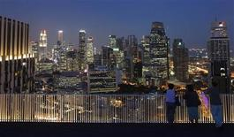 People look at the skyline of the central business district in Singapore in this April 25, 2013 file photo. REUTERS/Edgar Su/Files